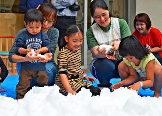大はしゃぎで雪遊びを楽しむ子どもたち=21日、南風原町の県立南部医療センター・こども医療センター