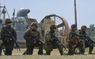 ボートで上陸した上での襲撃の訓練を展開する米兵と陸上自衛隊員=9日、金武町・ブルービーチ