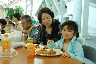 Aランチを頬張る家族=22日、沖縄市・コザ運動公園