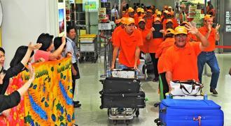 大きな拍手で出迎えられ、手を振り応えるニューカレドニアからの参加者=20日午後、那覇空港