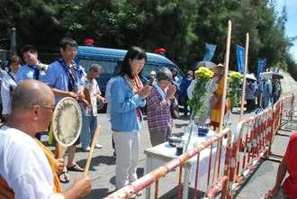 沖縄戦の犠牲者を悼み、手を合わせる市民たち=24日午前10時半ごろ、名護市辺野古の米軍キャンプ・シュワブゲート前