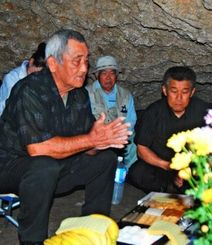 ガマの中に設けられた祭壇に手を合わせ、犠牲者の冥福を祈る遺族ら=2日午後1時すぎ、読谷村波平・チビチリガマ