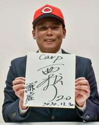 広島との入団交渉を終え、色紙を手にするトヨタ自動車の栗林良吏投手=30日、名古屋市