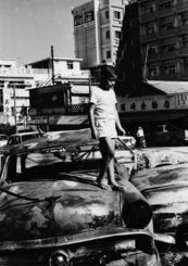 【この少年、捜しています】焼け焦げた米人車両のボンネットの上を歩く少年=1970年12月20日(国吉和夫さん提供)