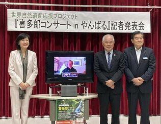 喜多郎さん(画面内)のコンサートをPRするカルティベイトの開梨香社長(左)沖縄海邦銀行の上地英由頭取(右)、比嘉明男理事長=日本郵便沖縄支社