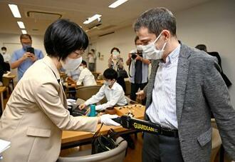 対局を中断し、金属探知機を使った抜き打ちの所持品検査を受ける棋士(右)=23日午後、東京都千代田区の日本棋院