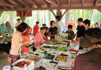 一品料理を持ち寄り、ゲームやおしゃべりで交流を楽しんだピクニック=アトランタ市郊外