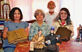 市川スミエさんの祖父母の着物を着せた人形の完成を喜ぶ母親の金城初子さん(中央)、友人の山内利江子さん(左)、人形作家の座間味末子さん(右)と夫の力さん(後列)=17日、沖縄市松本