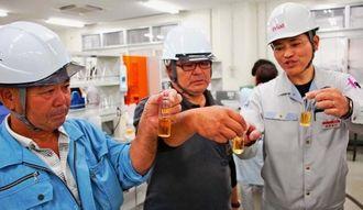 オリオンビールの儀間次長(右)から江島神力を使った新商品「琉球ホワイト」の説明を受ける玉城会長(中央)と小麦を生産した農家の玉城増生氏=5日、オリオンビール名護工場