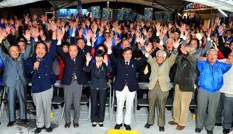 当選を確実とし、支持者とバンザイで喜ぶ稲嶺進氏(中央)=19日午後9時40分、名護市大中の選対本部