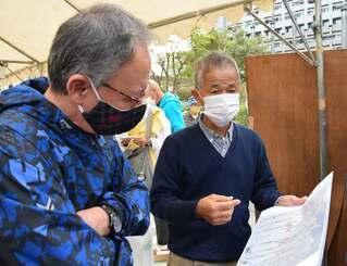 「ガマフヤー」代表の具志堅隆松さん(右)から遺骨収集の説明を聞く玉城デニー知事=6日午前、那覇市・県民広場