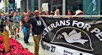 軍事化よりも教育が重要だと訴えパレードするベテランズ・フォー・ピース(VFP)の平和行進=13日、米イリノイ州シカゴ市内