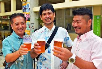 名護限定ビール「75―Beer」で乾杯する人たち=6日、名護市城・市営市場