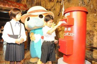 玉泉洞内に設置された郵便ポストに年賀状を投函する小学生=14日、南城市のおきなわワールド