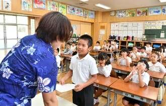 1学期を終え担任の先生から「よい子のあゆみ」を受け取る児童=10午前、沖縄市中の町小学校