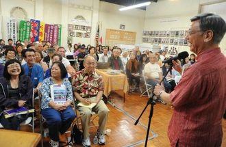 北米県人会メンバーらへ大会参加を呼びかける翁長雄志知事(右)=12日午前、ロサンゼルス市・北米県人会館