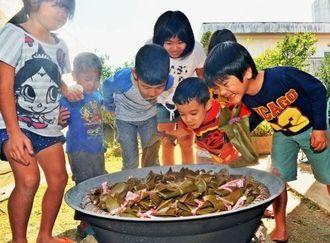蒸したムーチーに歓声を上げる子どもたち=16日午後、南城市大里(伊藤桃子撮影)