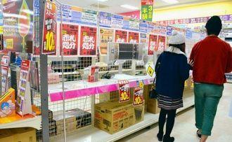 暖房器具売り場を訪れた買い物客。空になった陳列棚もあった=24日、エディオン那覇メインプレイス店