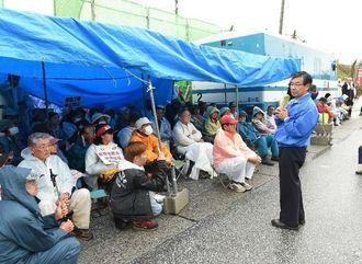 キャンプ・シュワブゲート前で早朝から抗議行動などを行う市民らを激励する稲嶺進名護市長(手前)=6日午前8時すぎ、名護市辺野古