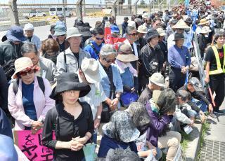 犠牲となった女性に黙とうをささげる集会参加者=29日午前、名護市のキャンプ・シュワブゲート前