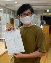 交付されたワクチンパスポートを手にする会社員=26日午前、東京都港区