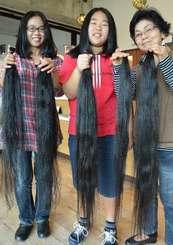 ばっさり切った髪の毛を手にする(左から)渡慶次直美さん、娘の花梨さん、ヘアドネーションを勧めた祖母の當真美江さん=沖縄市松本・美容室「ヘアーDco」