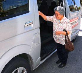 南城市のデマンドバスに乗る渡恵美さん。買い物や通院に便利と話す=市の大里グリーンタウン