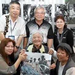 1962年に撮影された写真に自分の姿を見つけ、それを手にする古堅千枝さん(中央)と家族=9日、那覇市樋川の農連市場