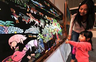 ふしぎ! 「ブタさんが光ってる!」と作品を指さす女の子=浦添市民体育館