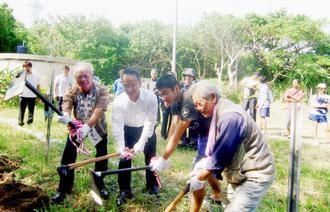 力を合わせて桜の幼木を植える鳩間島の人々=2012年11月(冨里勝行さん提供)