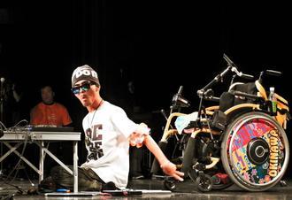初めてDJを披露し、会場を沸かせる瑞慶山良さん。Tシャツや車いすも自分でデザインした=9日、沖縄市のコザミュージックタウン音市場