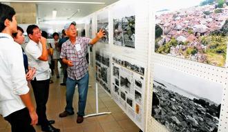 会場で出会った人同士で、写真に写る82年前の糸満を巡る会話が弾んでいた「1935沖縄・糸満 写真にみる故郷」展=22日、糸満市役所