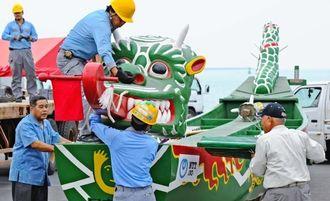 展示のため陸揚げされた爬龍船を組み立てる作業員ら=1日午前11時半ごろ、那覇市・那覇新港