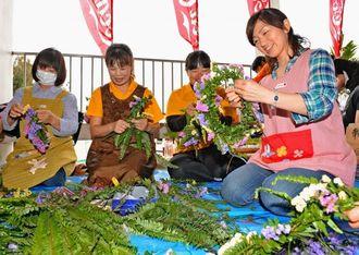 「頑張って完走してほしい」とエールを込め、花冠をつくる保育士ら=19日午後、宮古島市総合体育館前