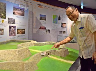 座喜味城跡の模型や歴史を伝える展示をPRする上地克哉課長=17日、読谷村・世界遺産座喜味城跡ユンタンザミュージアム