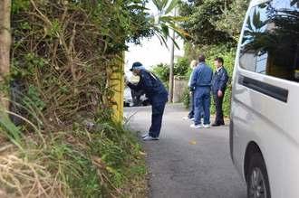 犯行現場近くの自動販売機から指紋を採取する警察官=3日午前8時51分、うるま市川崎