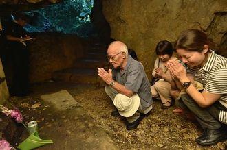壕の中で手を合わせ、戦没者の冥福を祈る家族連れ=23日午前8時すぎ、糸満市摩文仁・沖縄師範健児之塔