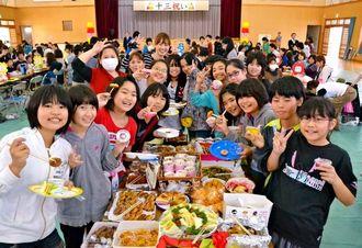 十三祝いの手作り料理に飛びつく5年生たち=7日、仲西小体育館