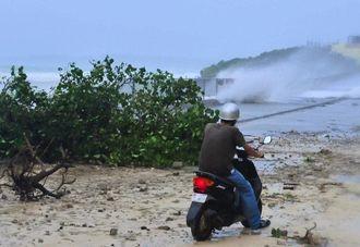 道路に高波が押し寄せ、停止するバイクの男性=午後3時40分、本部町崎本部(松田興平撮影)