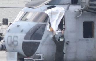 米軍普天間飛行場のCH53E大型輸送ヘリ。窓のない部分をシートで覆う作業員=13日午前11時52分、宜野湾市(田嶋正雄撮影)