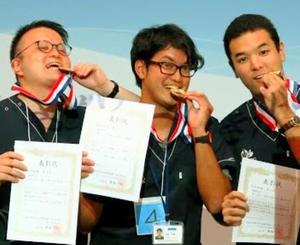 表彰式で金メダルをかじる琉球大学の(左から)能美康彦さん、金城英樹さん、仲間海人さん=7月31日、大阪府内(又吉哲太郎さん提供)