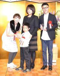 第7回MOE絵本屋さん大賞2014で1位となり、タレントの豊田エリーさん(左)から記念の盾を受け取る(左2人目から)安里有生君と母親の真弓さん、絵本作家の長谷川義史さん=19日、東京ドームホテル