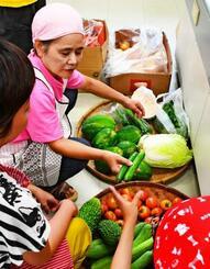 毎月1回の「いどばたごはん会」。地域から新鮮な野菜が届けられる=那覇市繁多川公民館