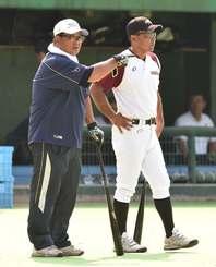大蔵宗元監督(右)の横で、嘉手納ナインの指導に当たる小倉清一郎コーチ=大阪市・南港中央球場