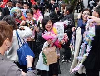 家族や在校生に祝福されて花道を歩く卒業生=1日午後、西原高校