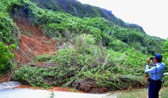 吉野海岸へと向かう道路の土砂崩れ現場を確認する宮古島署の警察官=6日、宮古島市城辺新城