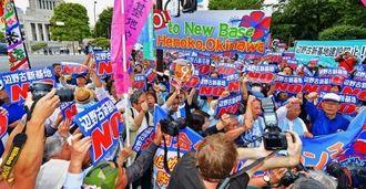 名護市辺野古での新基地建設に反対し、国会議事堂(左奥)前で気勢を上げる人々=24日午後、東京・永田町