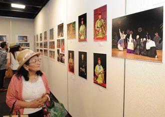 琉球舞踊と組踊の写真に見入る来場者=26日、那覇市久茂地・タイムスギャラリー