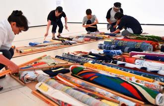 13日から開催される「90回記念国展工芸沖縄展―黎明から現代 匠の系譜」に向けた準備の様子です=10日、県立博物館・美術館
