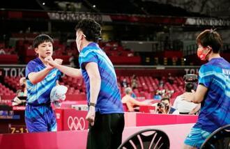 男子団体1回戦 オーストラリア戦の第2試合で勝利し、倉嶋監督(手前)とタッチを交わす張本智和。右は丹羽孝希=東京体育館